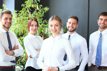 Photo pour Happy young business woman standing in front of her team - image libre de droit