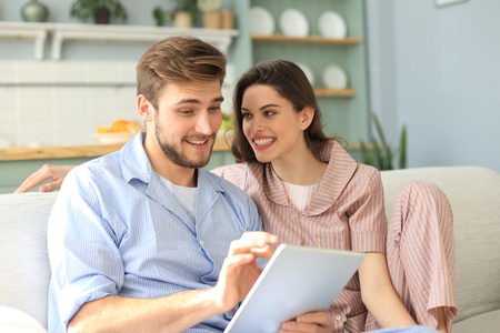 Photo for Young couple in pajamas watching media content online in a tablet sitting on a sofa in the living room - Royalty Free Image