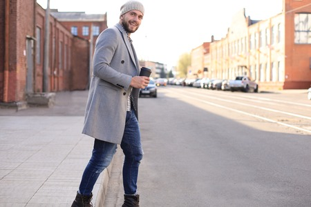 Photo pour Handsome young man in grey coat and hat crossing the street with a cup of coffee - image libre de droit