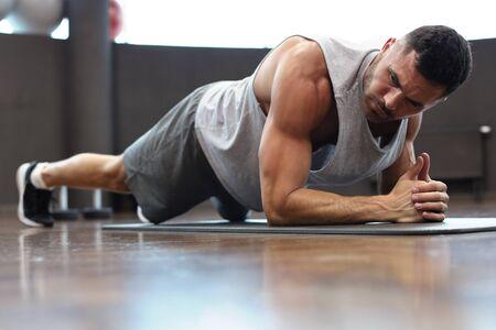 Foto für Portrait of a fitness man doing planking exercise in gym - Lizenzfreies Bild