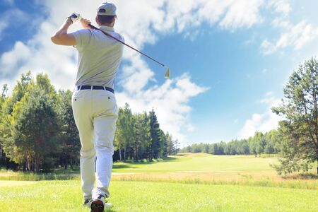 Foto de Full length of golf player playing golf on sunny day. Professional male golfer taking shot on golf course - Imagen libre de derechos