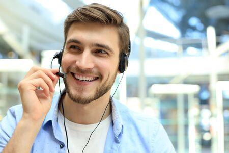 Photo pour Smiling friendly handsome young male call centre operator - image libre de droit