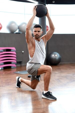Photo pour Fit and muscular man exercising with medicine ball at gym. - image libre de droit