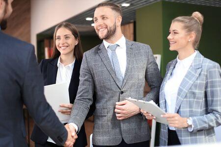 Photo pour Business partners handshaking over business objects on workplace. - image libre de droit