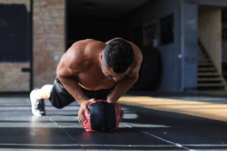 Photo for Fit and muscular man exercising with medicine ball at gym - Royalty Free Image
