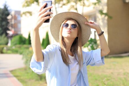Photo pour Beautiful young blonde girl using mobile phone while standing outdoors - image libre de droit