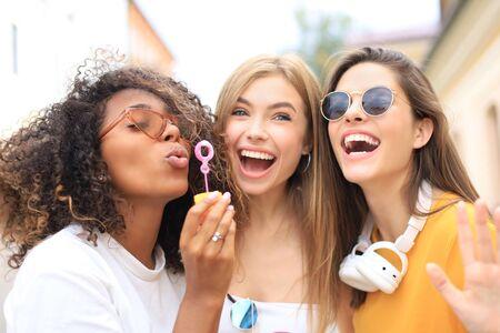 Photo pour Three happy beautiful women blowing soap bubbles in city street - image libre de droit