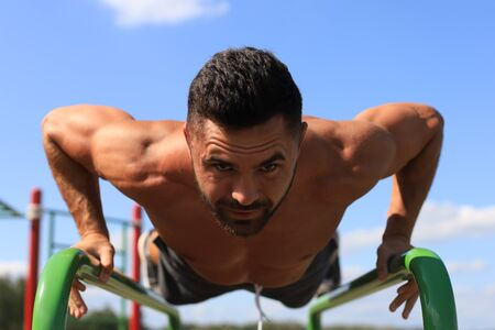 Photo for Strong sporty man holding plank on bars outdoors. Work out. - Royalty Free Image