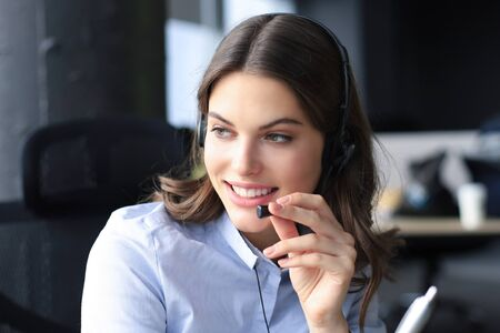 Photo pour Beautiful smiling call center worker in headphones is working at modern office. - image libre de droit