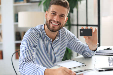 Photo pour Smiling man sitting in office and pays by credit card with his laptop - image libre de droit