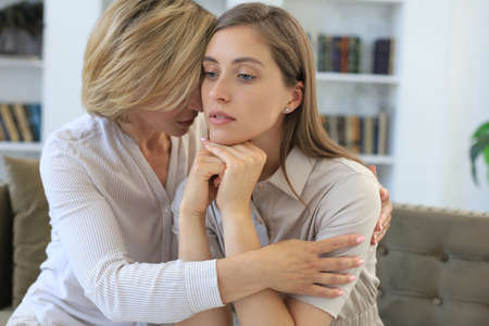 Photo pour Concerned middle aged mother and adult daughter sit on couch having serious conversation, listen to her sharing problems. - image libre de droit