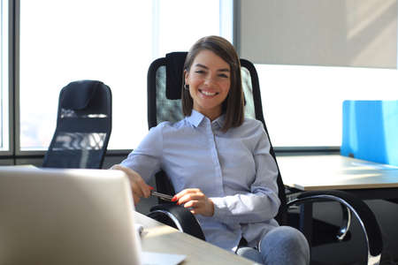 Photo pour Beautiful smiling business woman is sitting in the office and looking at camera. - image libre de droit