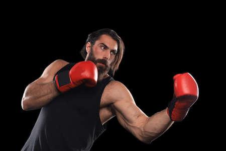 Photo pour Kickboxer man fighting against black background. Sport concept - image libre de droit