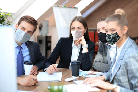 Foto de Group of young business people working, communicating while sitting at the office desk together with colleagues in preventive masks during epidemy. - Imagen libre de derechos