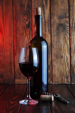 Photo for A glass of red wine with a bottle and a candle on a wooden background. - Royalty Free Image