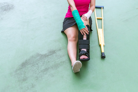 Injured woman wearing sportswear painful arm with gauze bandage, arm cast and wooden crutches sitting on floor.
