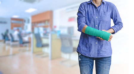 Photo pour worker woman accident on arm with green arm cast on blurred business office working space background - image libre de droit