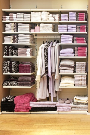 Big storage space with towels on shelf and bathrobes on hangers