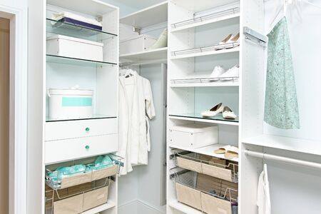 Detail of large walk in closet with modern wardrobe on hangers