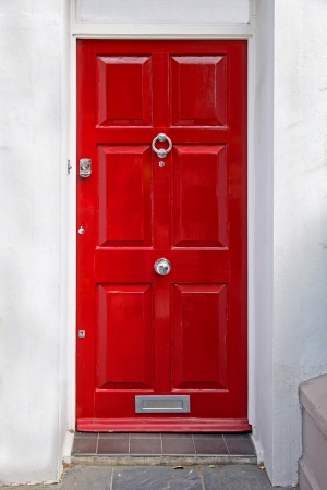 Red entrance door in front of residential house