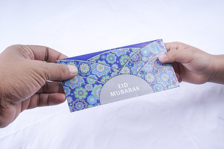 Giving and receiving money packet during Eid Fitri.