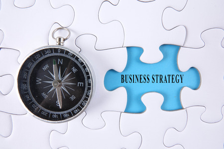 Jigsaw puzzle and compass with BUSINESS STRATEGY words.