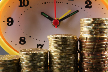 TAX TIME CONCEPT. Yellow clock and stack of coins over black background.