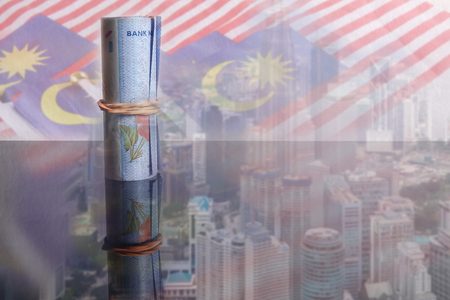 Photo pour 1 Malaysian Ringgit banknotes over a blur background of Malaysia flags and cityscape. - image libre de droit