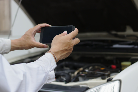 Photo for Hands of mechanic man taking a picture with mobile smart phone against car in open hood at the repair garage. - Royalty Free Image