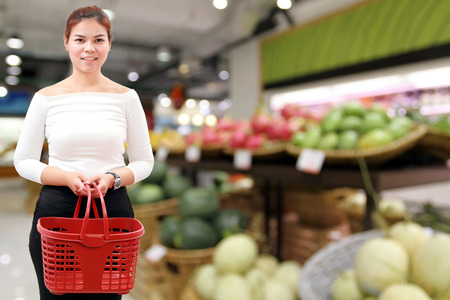 happiness, consumerism, sale and people concept - smiling young woman Asian with shopping basket and buy vegetable/fruit at supermarket/mall