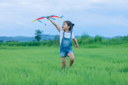 Foto de Asian child girl with a kite running and happy on meadow in summer in nature - Imagen libre de derechos