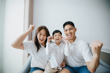 Photo pour Excited and Happy family with arms raised while watching television at home - image libre de droit