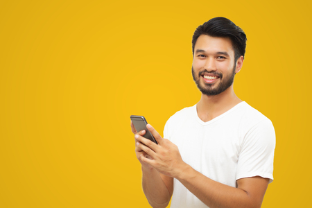 Photo pour Asian business man handsome man with a mustache, smiling and laughing and using smart phone on yellow background - image libre de droit