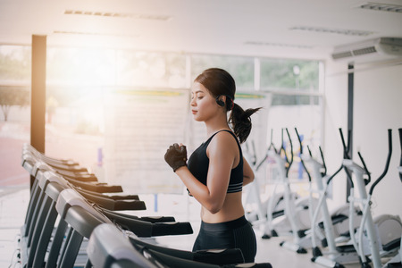 Foto de Asian women running sport shoes at the gym while a young caucasian woman is having jogging on the treadmill - Imagen libre de derechos