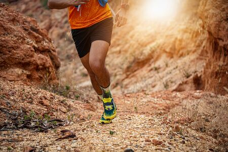 Photo pour A man Runner of Trail. and athlete's feet wearing sports shoes for trail running in the forest - image libre de droit
