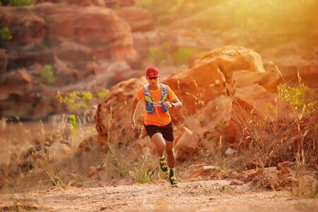 Photo pour A man Runner of Trail and athlete's feet wearing sports shoes for trail running in the forest - image libre de droit