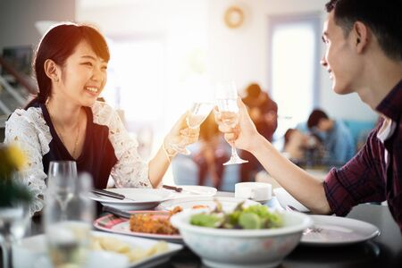 Photo for Asian young couple enjoying a romantic dinner  evening drinks while sitting at the dinning table on the kitchen together - Royalty Free Image