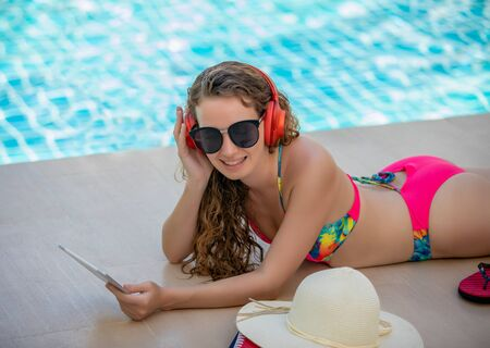 Photo for Women wear bikinis, read books and listen to music at the summer recreation pool. - Royalty Free Image
