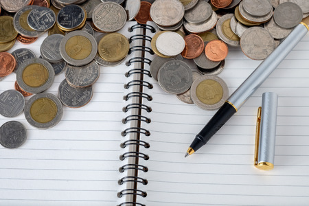 business finance. save money for investment concept coins and pen