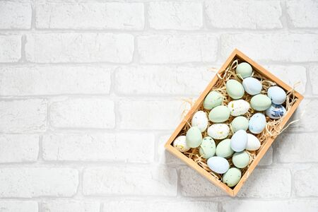 Photo pour Easter background flat lay with pastel chocolate eggs and rabbit wood figure on white brick background, text copy space, happy and funny season in april. - image libre de droit