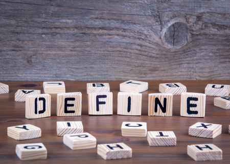 Define from wooden letters on wooden background