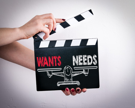Wants and Needs Balance. Female hands holding movie clapper.
