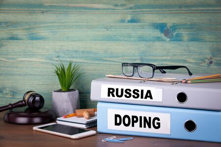 Russia and Doping. Two binders on desk in the office. Fraud and justice.