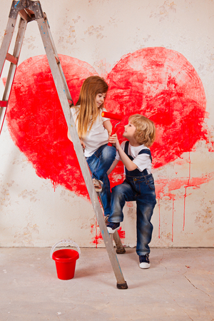 Foto de boy and a girl in jeans and a white T-shirt, look at each other, with a paintbrush and a bucket stand on a ladder paint the wall in red, a big heart - Imagen libre de derechos