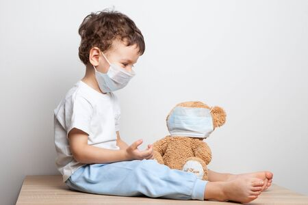 Photo pour a child in a medical mask put on a respiratory mask for his favorite toy - a teddy bear. spread of coronavirus. hygiene. security measures . health care concept. child protected from the virus. - image libre de droit