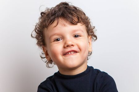 Photo for spoils a cute curly boy, a toddler. Funny smile. A child in a black T-shirt on a white background, isolated. - Royalty Free Image