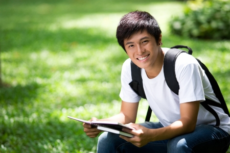 Young handsome Asian student thinking and smile in outdoor
