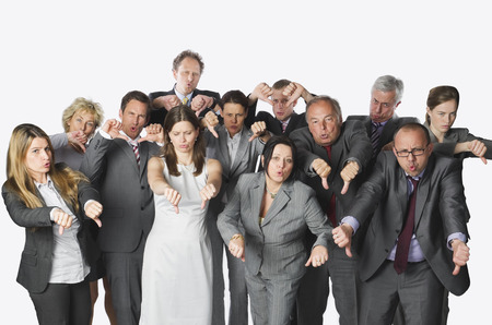Large group of business people showing thumbs down against white background
