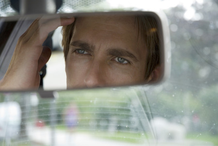 Young man looking into rear view mirror