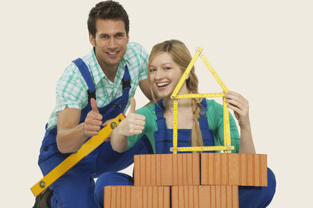 Man and woman behind stack of bricks holding folding ruler and spirit level thumbs up